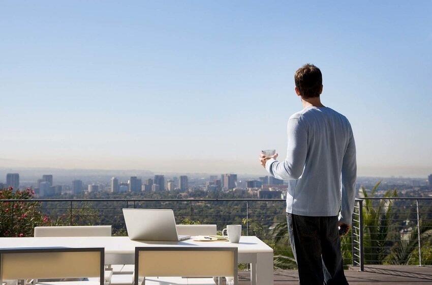 Man using laptop on balcony overlooking city